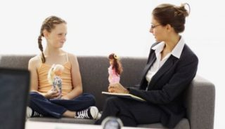 a young girl and an ADHD specialist sitting on a couch both holding a doll talking to each other