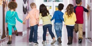 a group children walking away happily on the hallway and holding each other's hands
