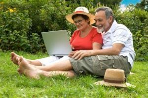 an image of a senior citizen couple sitting on a green grass lawn happily using a laptop