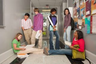 an image of a group of students sitting and standing along the school hallway