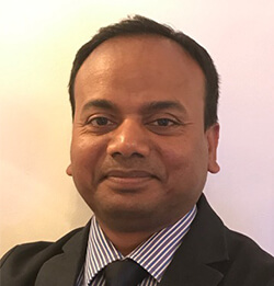 a headshot image of a man wearing black suit, inner stripes with black necktie which is Dr. Ashish Kumar