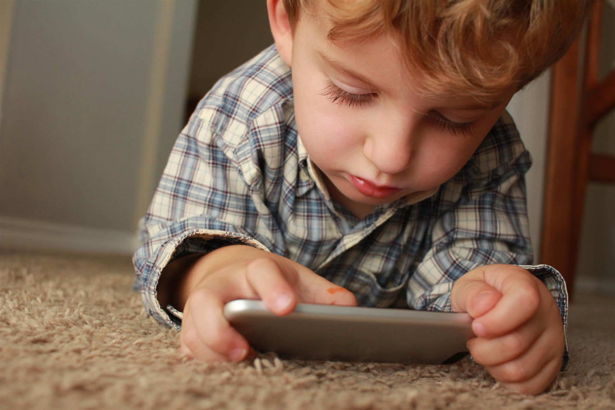 a close up image of a child laying down on a carpet closely looking at a mobile device while holding it with both hands