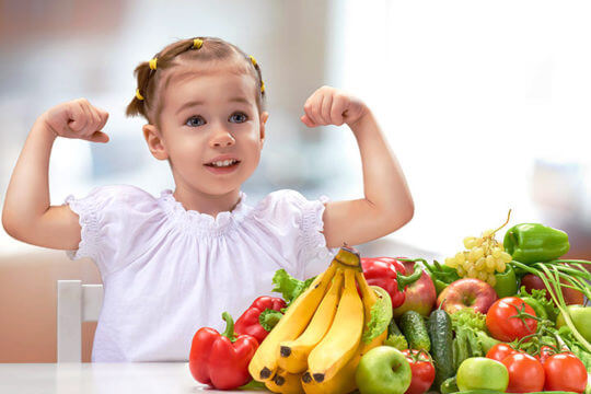 food at the top of the table with a child doing a flex pose