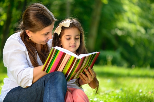a woman and a child holding a book