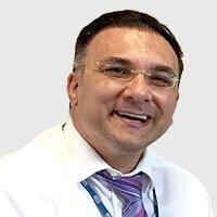 a man wearing eyeglasses smiling happily