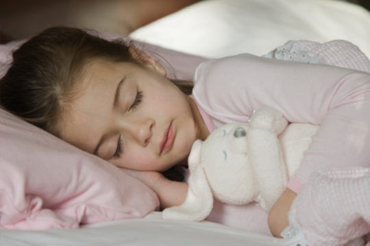 a child peacefully sleeping on a bed
