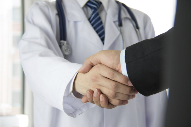 a doctor and a man doing a shakehands