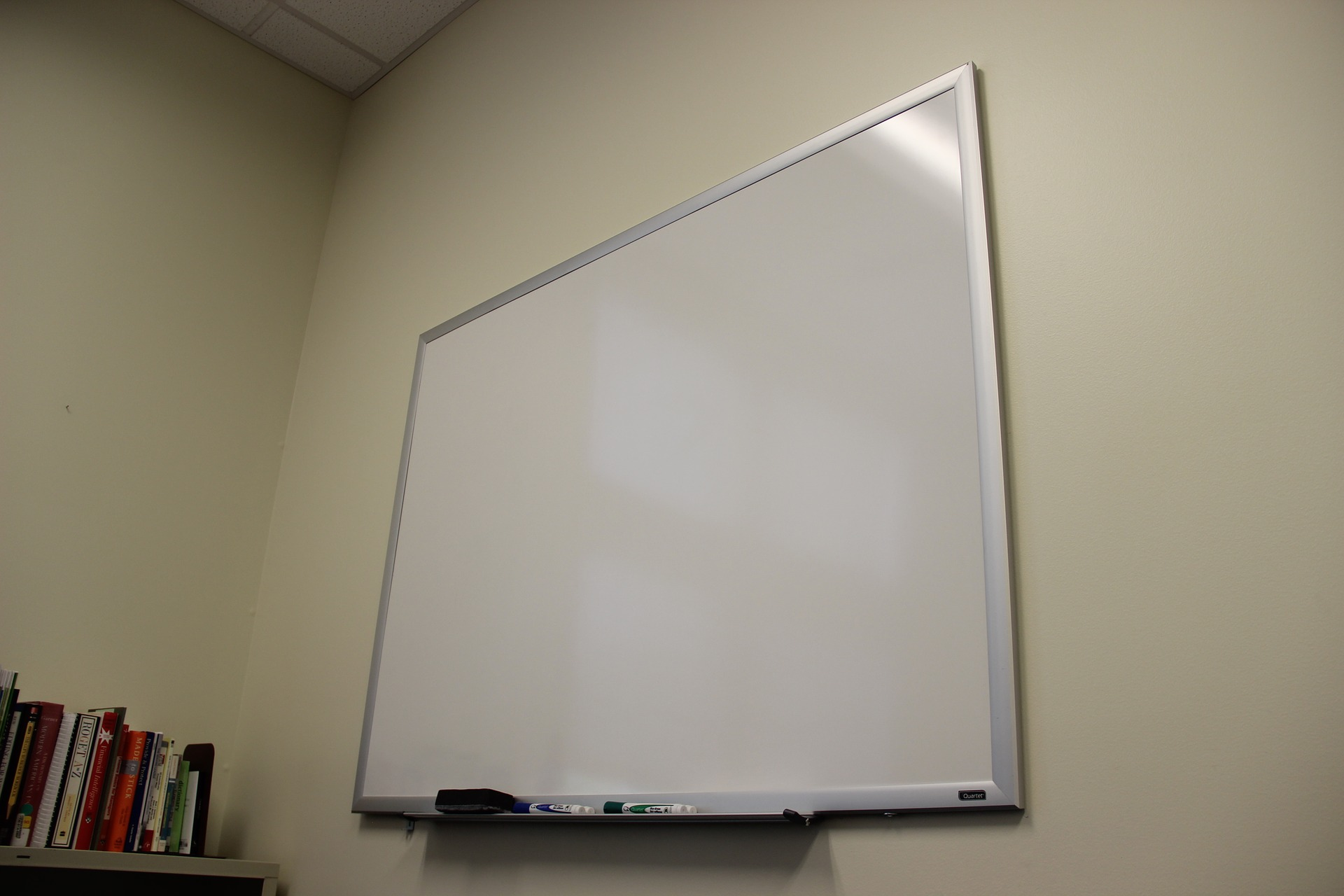 a clean whiteboard attached on the wall inside room with some books place properly on shelf