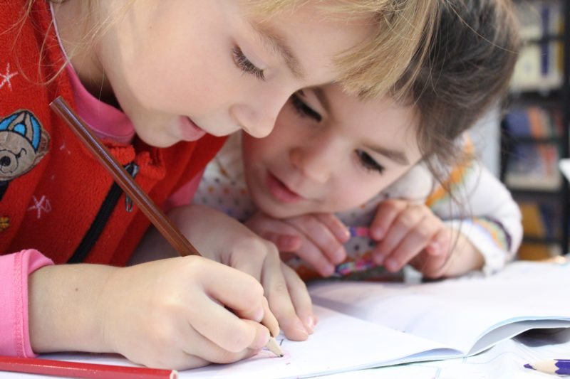 two young girls writing on a clean notebook