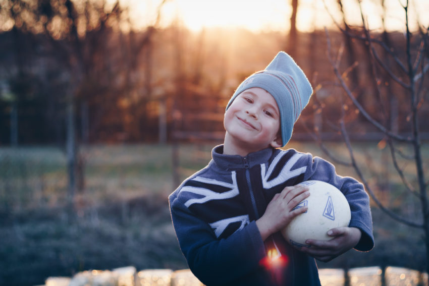 a child wearing bonnet and sweater holding a soccer ball