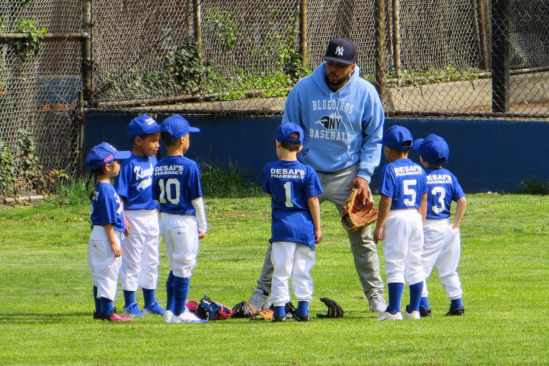 a kid's baseball team huddling with their coach wearing their blue and white baseball uniforms