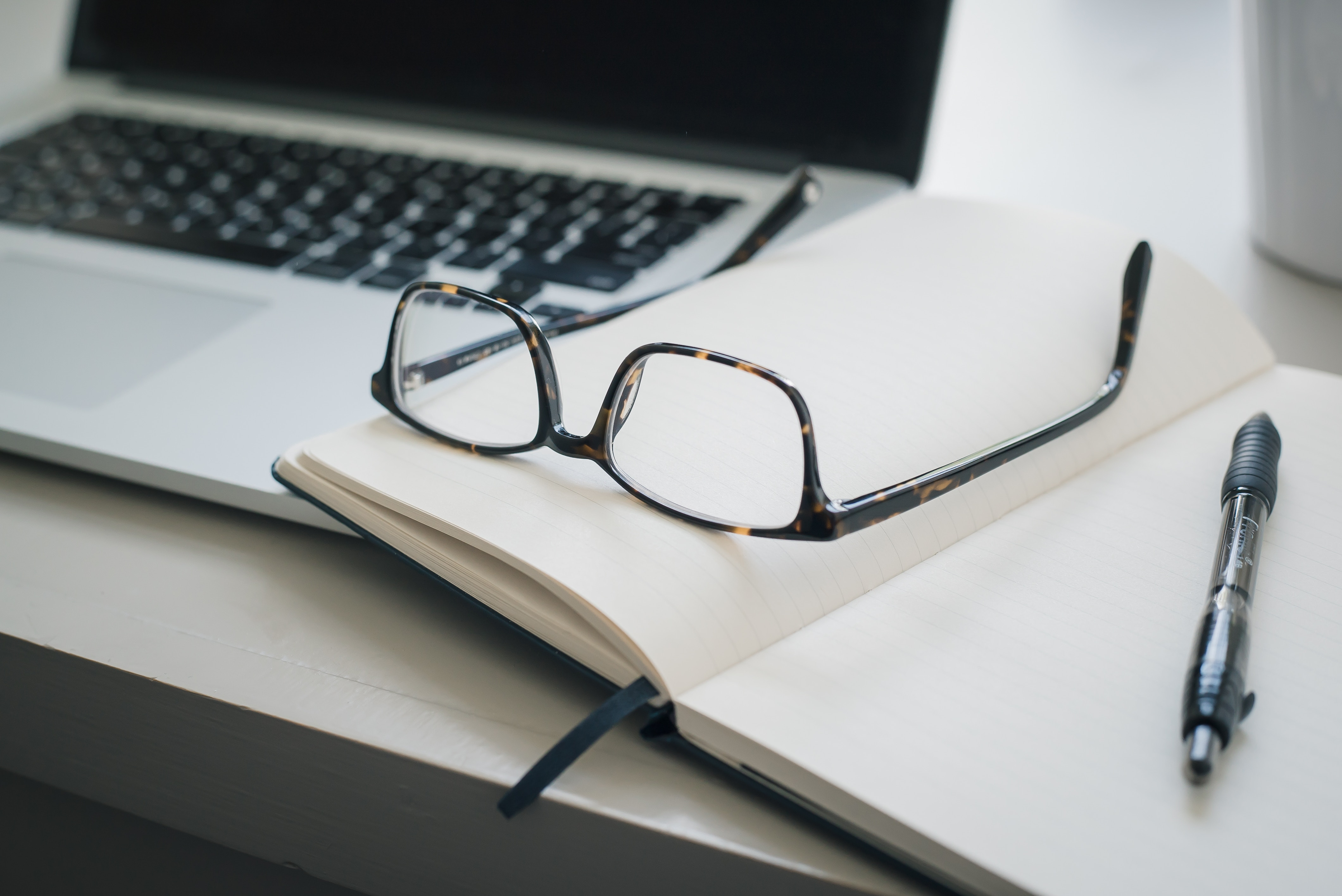 a laptop; eyeglasses; pen and notedbook on top of table