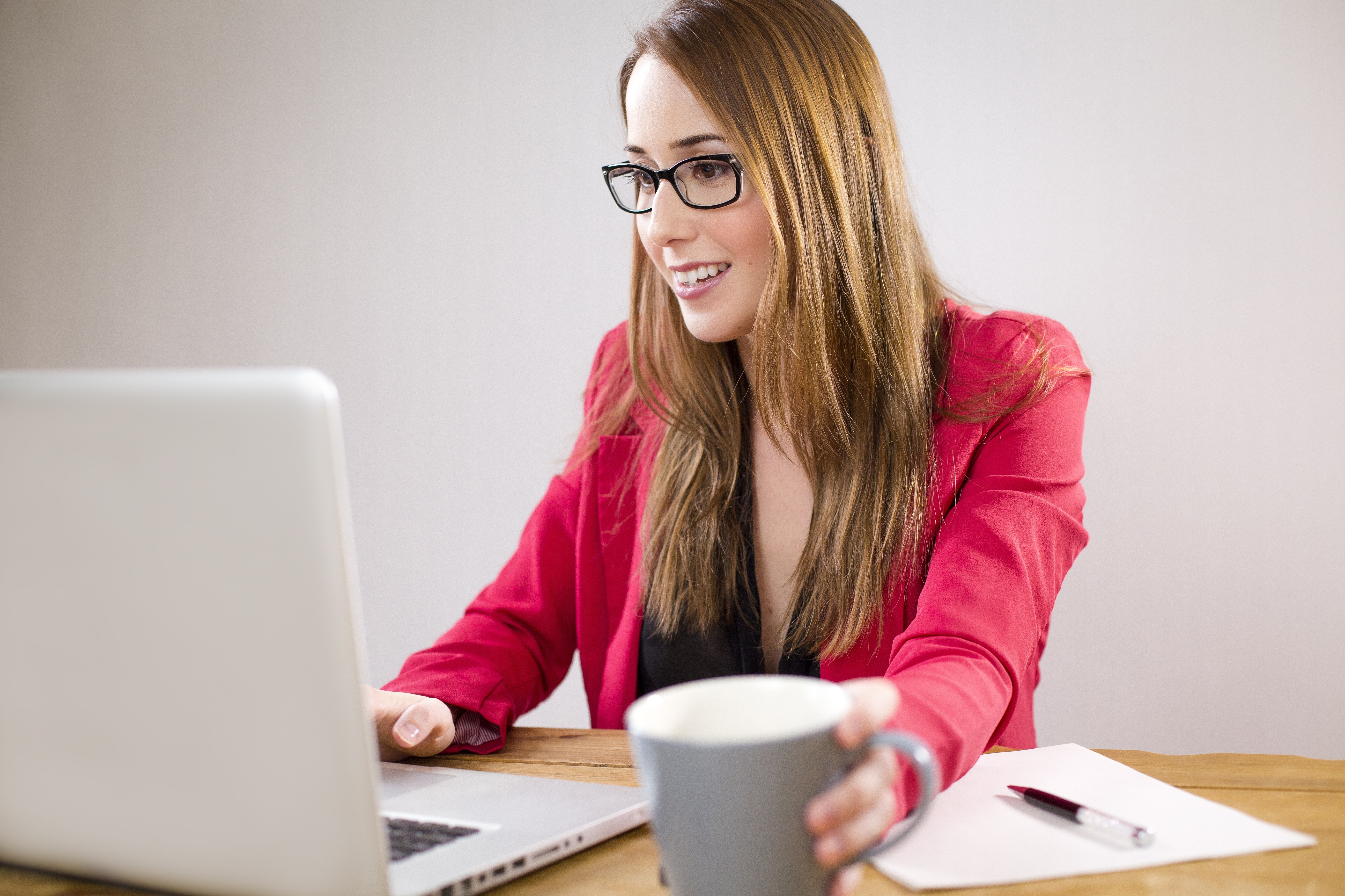 a woman sitting and smiling in fron of her laptop inside a clean office