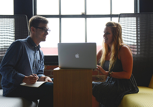 A man and woman sitting on a chair, The woman is looking at the man while the man is looking at the laptop on the desk while taking notes.