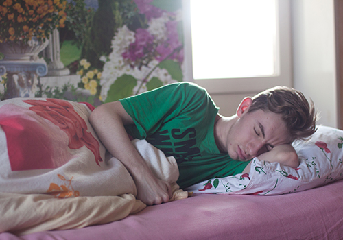 A man wearing a green shirt whose lying on the bed.