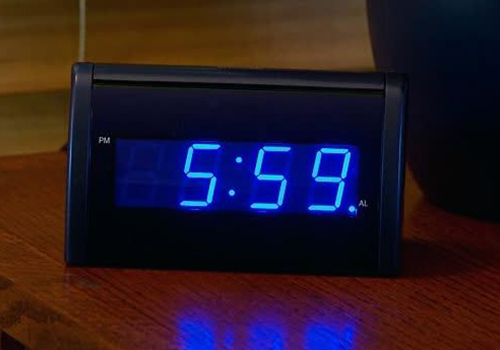 A small, black digital alarm clock having a blue colour highlighting the numbers.
