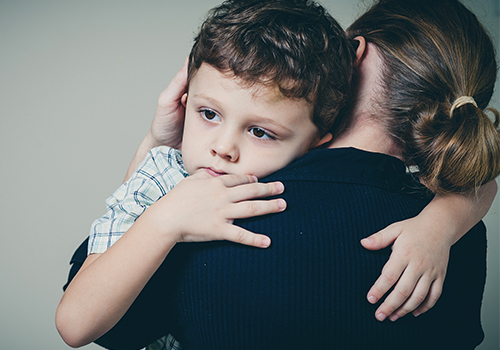 A little boy wearing a polo while hugging her mother.
