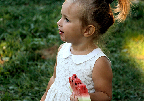A little girl, wearing a white dress with a watermelon on her left hand.