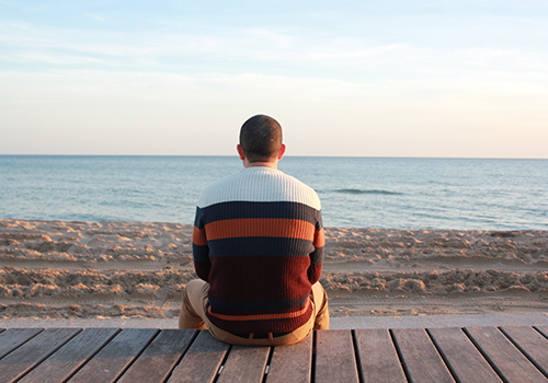 An adult man wearing a stripe sweatshirt, sitting down on a wood while facing the shore.