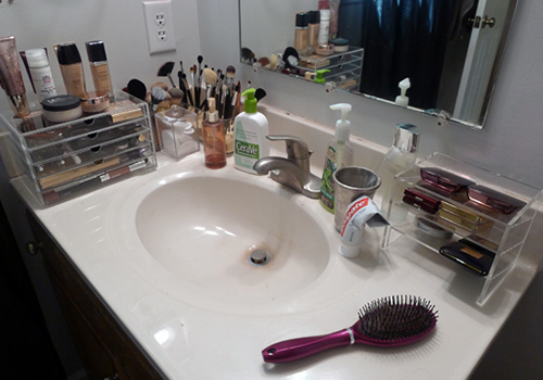 An arrange order of a make up kit on top of a washbasin in a bathroom.