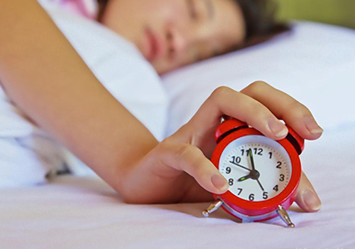 A blurry image of a girl lying on her bed while her hand is holding a red alarm clock.