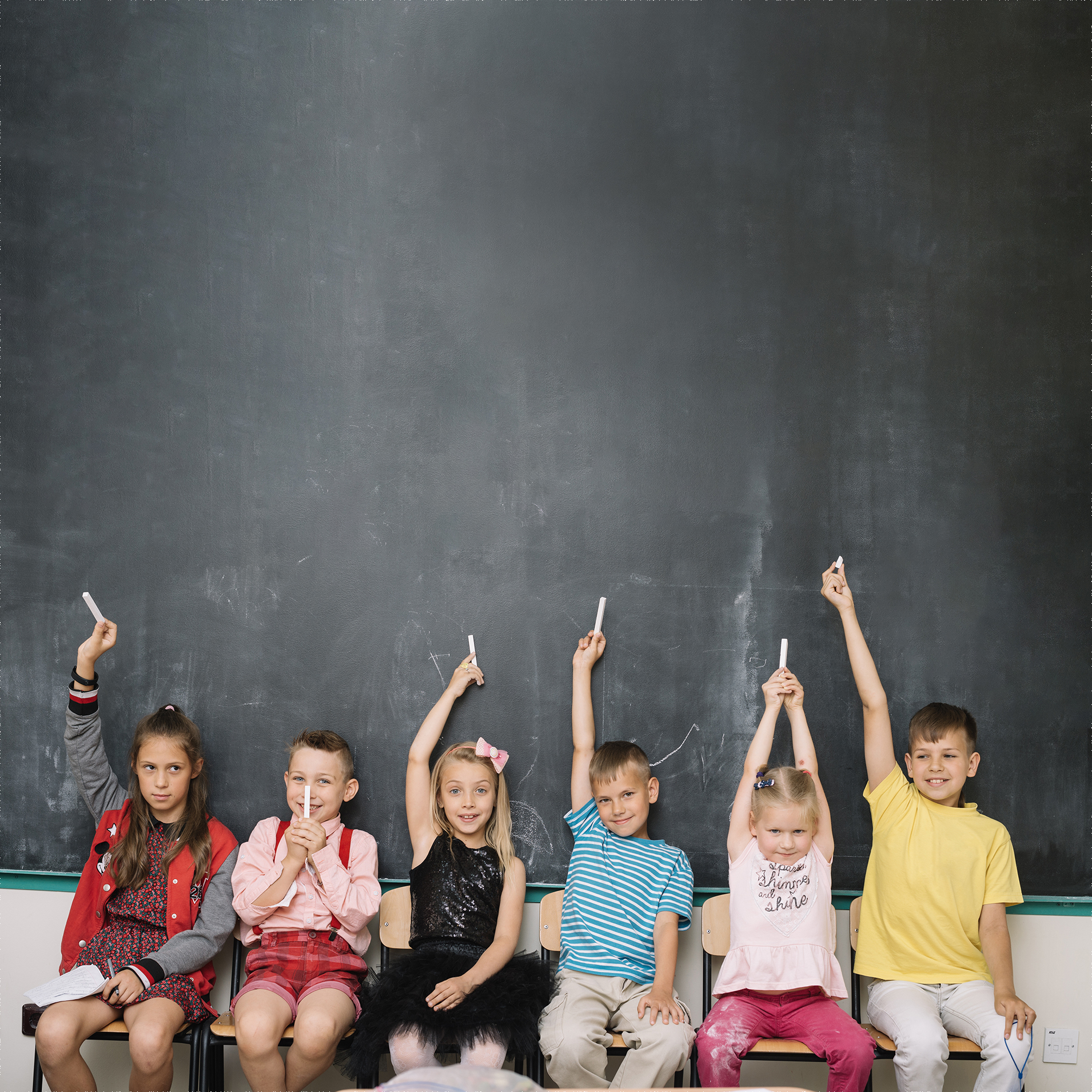 A group of children sitting in a chair, each one of them is holding a chalk and their background is a wide blackboard