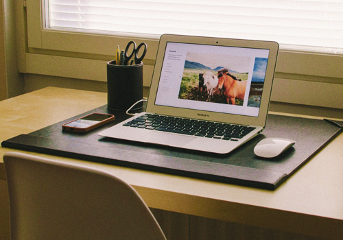 a wooden table with a laptop, mouse, cellphone and an organize ballpens relates to a clean and clear desk