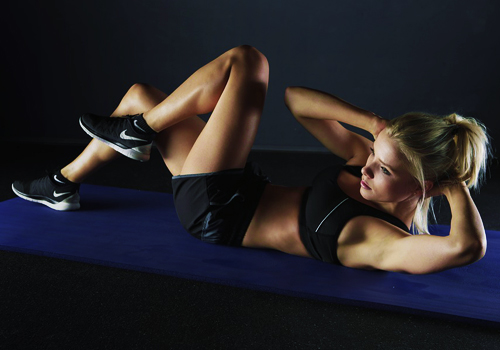 a woman laying on a blue mat doing an excercise wearing a black sportsbra