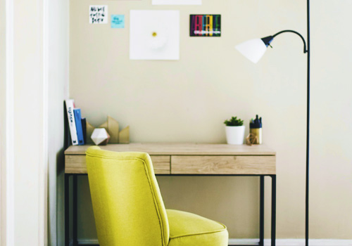 a yellow chair and a lamp with a wooden table and a piled of books on top