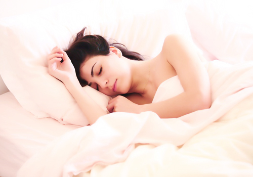 a woman sleeping on a white bed while covering her body with a white blanket