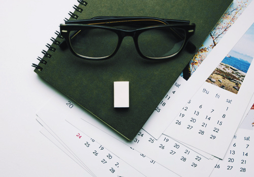a daily calendar with a green notebook place on top with a black eye glasses;