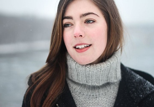 a smiling woman wearing a gray and black sweater which relates to acceptance