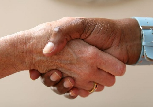 one hand wearing a ring and the other hand wearing a watch while shaking hands with each other