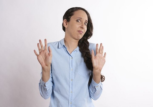 a woman wearing a skyblue polo shirt raising her hand which relates to denial