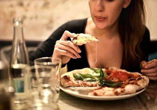 a woman eating an Impromptu Breakfast Pizza