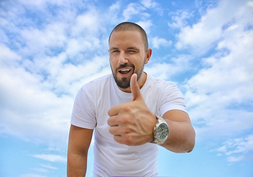 a man with his thumb up wearing a white shirt which relates that not all adhd thinking is bad