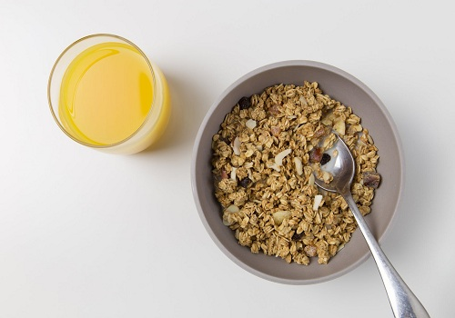 an oatmeal and a glass of juice place on a white table