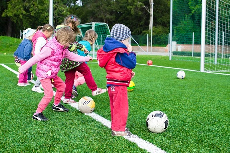 a group of children doing soccer sports in the field