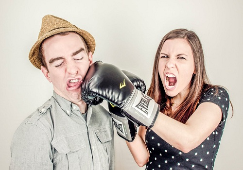 a woman wearing boxing gloves punching the man's face
