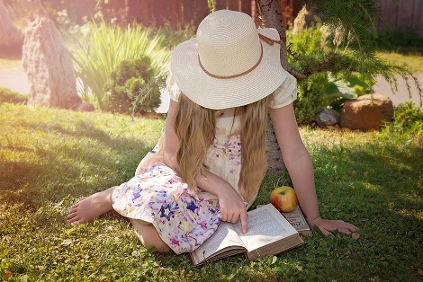 a child sitting on a grass relaxing while reading a book