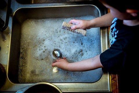a boy doing chores like washing plates