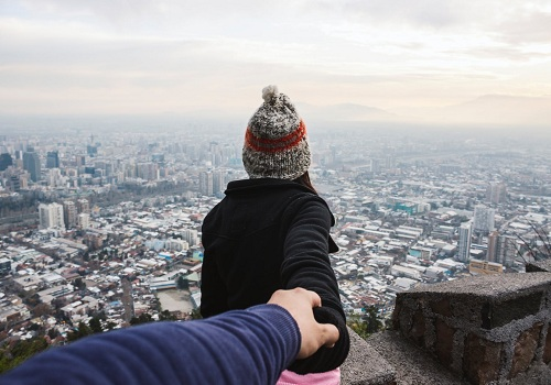 a woman holding the hand of a her man facing the city