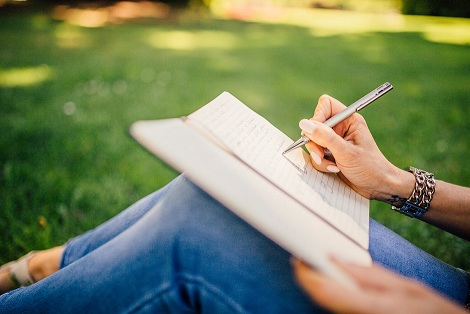 a woman sitting in the grass with a notebook and write something