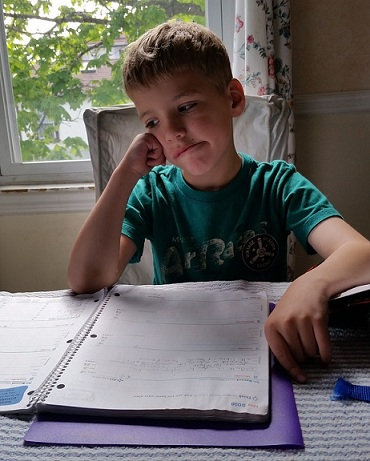 a boy doing his homework with a sad expression