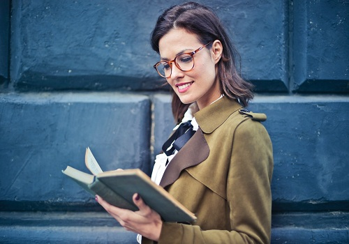 a woman wearing an eye glasses and brown suit while reading a book