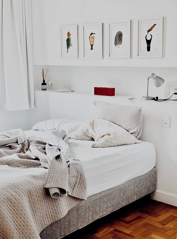 a bed with messy white bed sheet and pillows