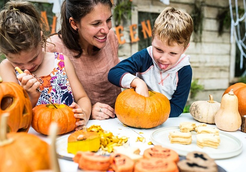 two children and a woman carving the pumpkin