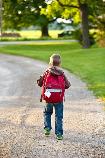 a boy with a backpack walking on the road