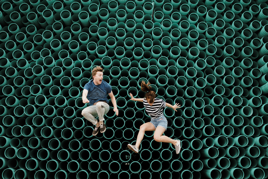 a man and a woman jumping around the small green circles