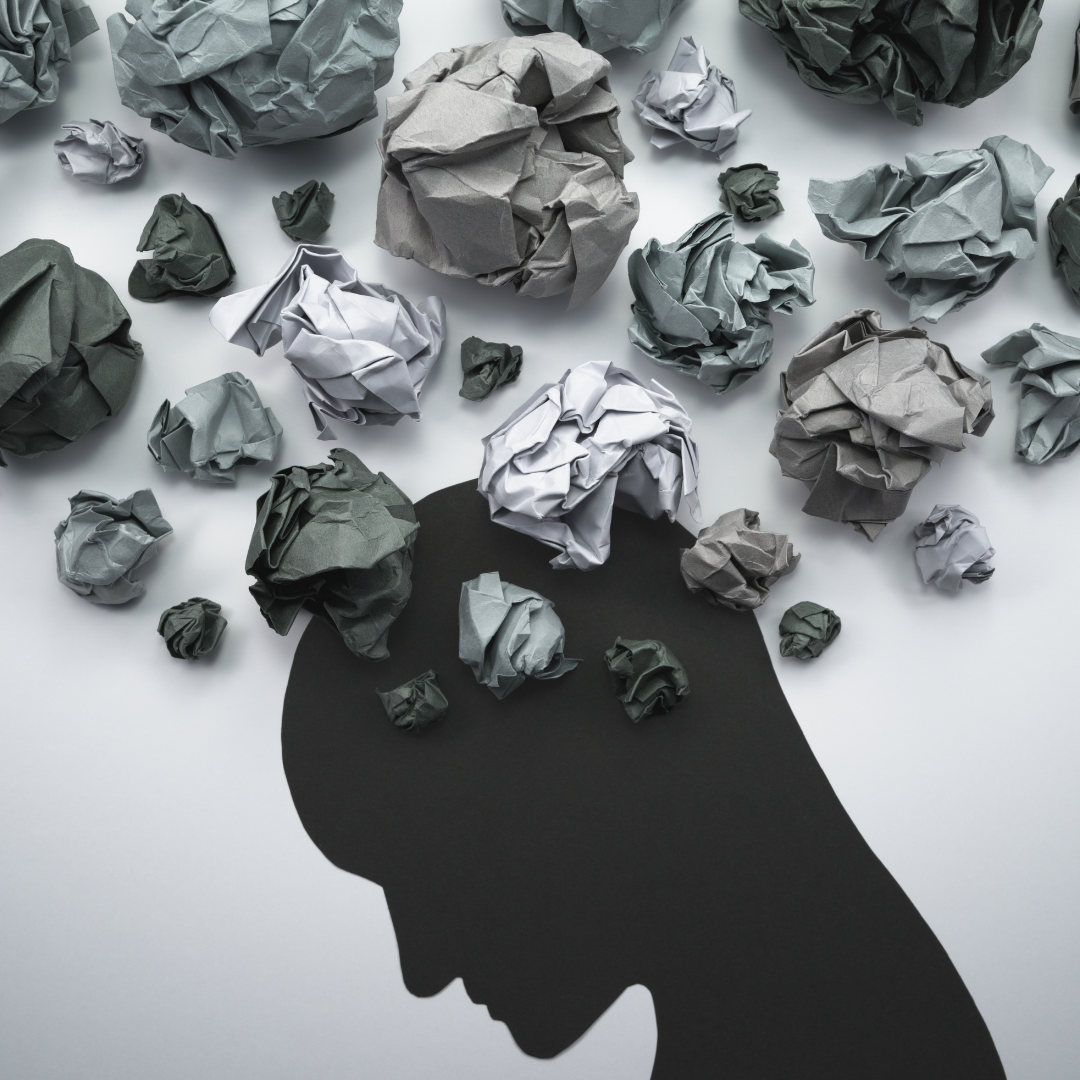 silhoutte of a person with crumpled papers on their head